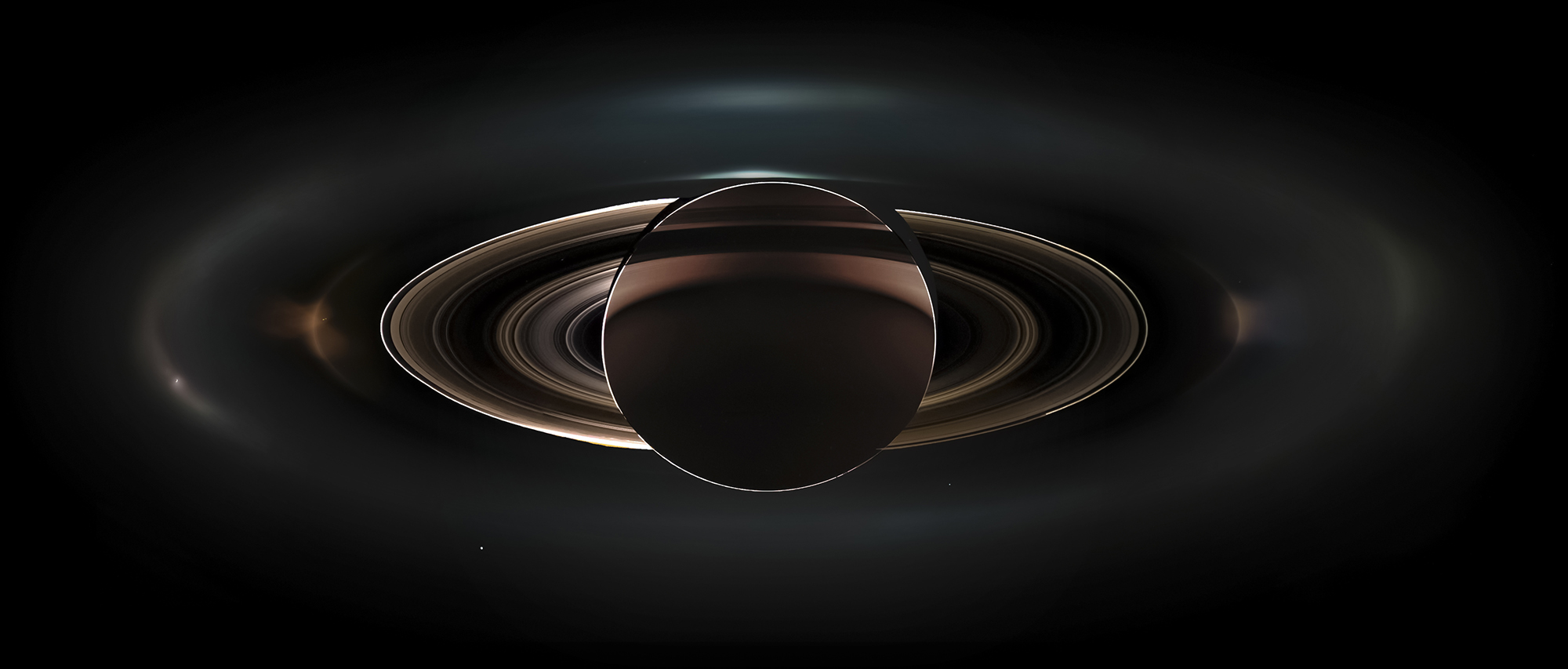 Панорамная фотография Сатурна, полученная 19 июля 2013 года аппаратом Кассини. В разряженном кольце слева - белая точка это Энцелад. Земля видна ниже и правее центра снимка.