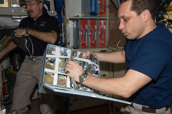 Российский космонавт Антон Шкаплеров выбирает продукты из пищевого контейнера