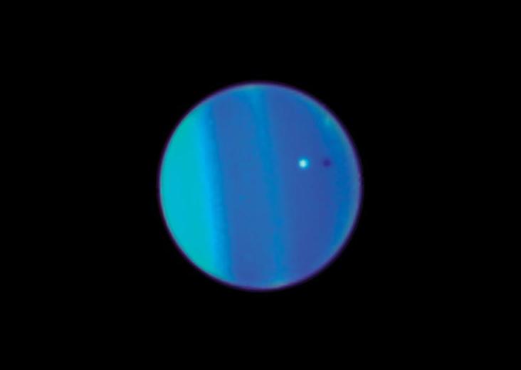 Спутник Ариэль на фоне облачного слоя планеты