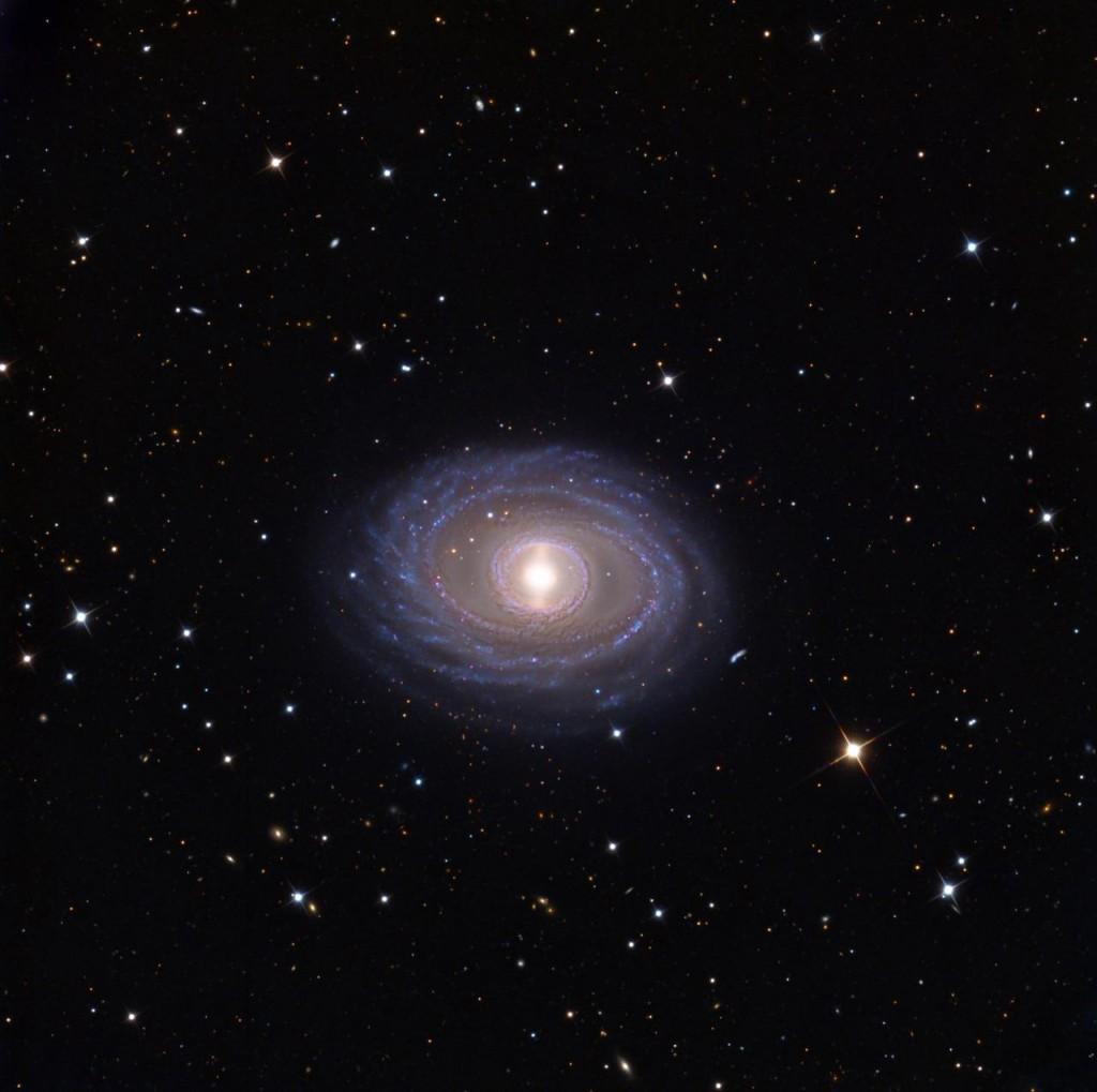 Галактика NGC 1398 - спиральная галактика с плотным внутренним кольцом, окружающим яркий центр ядра