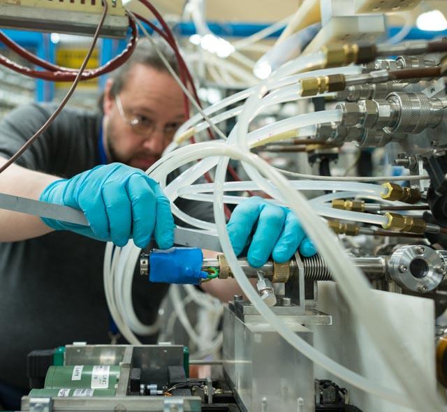 Физик Детлеф Кюхлер измеряет положение печи внутри источника ионов
